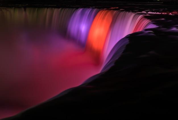 Cataratas do niágara iluminadas à noite por luzes coloridas