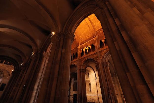 Catedral com arcos e colunas altos e iluminação artificial em corredores escuros