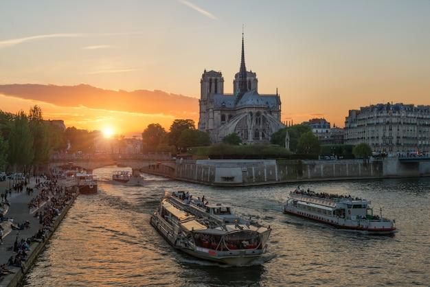 Catedral de notre dame de paris com o navio de cruzeiros no rio de seine em paris, france.