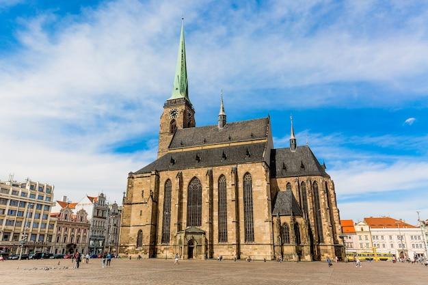 Catedral de são bartolomeu na praça principal de plzen com céu azul e nuvens em dia de sol. república tcheca, pilsen