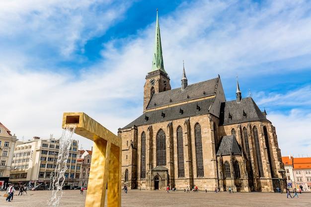 Catedral de são bartolomeu na praça principal de plzen, com uma fonte em primeiro plano contra o céu azul e nuvens dia ensolarado.