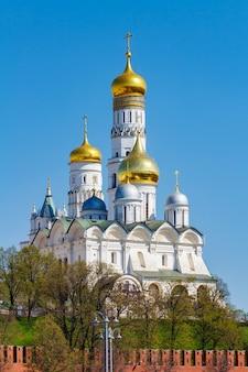 Catedral do arcanjo e ivan, o grande campanário contra a parede do kremlin de moscou na manhã ensolarada de primavera