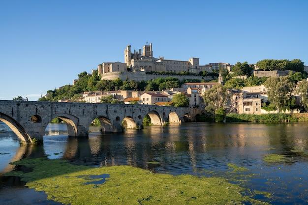 Catedral gótica no topo de uma colina em uma cidade com um rio e uma ponte de pedra para cruzá-la. narbonne frança