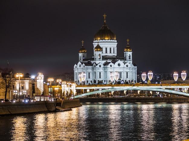 Catedral iluminada de cristo salvador, emoldurada com luzes de rua de estilo antigo da ponte do patriarcado à noite