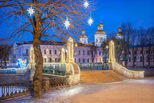 Catedral naval de nikolsky e estrelas festivas em uma árvore em são petersburgo e a ponte krasnogvardeisky sob o céu azul noturno