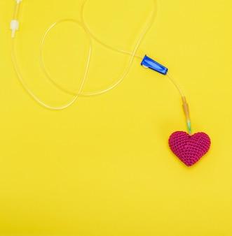 Cateter plástico com agulha e coração vermelho