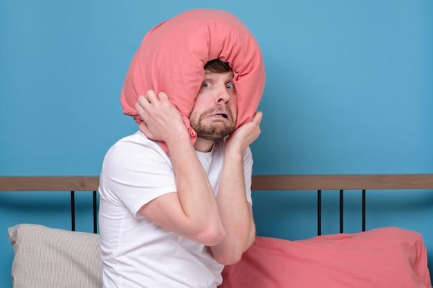 Cauacsian jovem com travesseiro na cabeça na cama com medo
