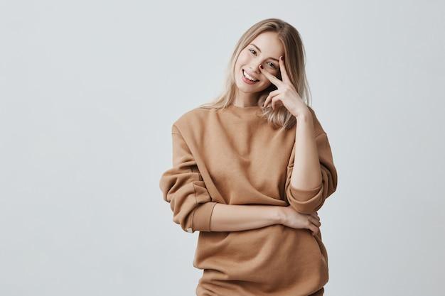 Caucasiana atraente jovem fêmea atraente, com longos cabelos loiros vestida com roupas casuais, sorrindo amplamente durante uma conversa interessante. jovem mulher expressando emoções positivas