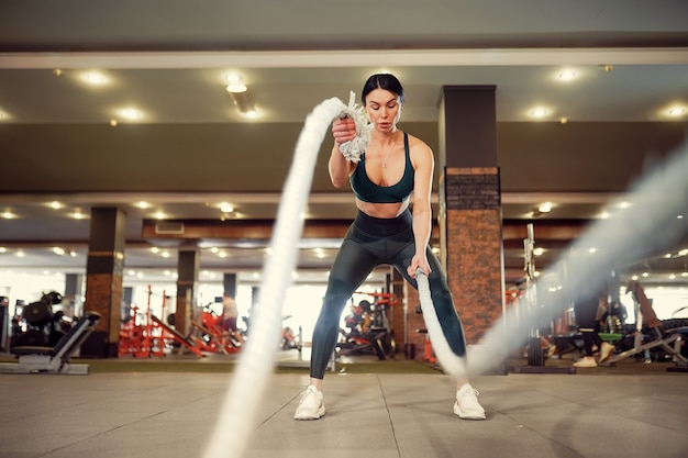 Caucasiana cabe mulher vestida de sportsoutfit fazendo exercícios com cordas de batalha no ginásio.