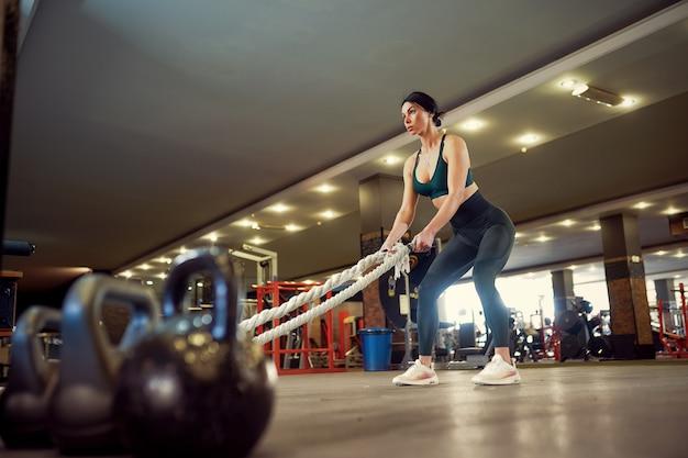 Caucasiana cabe mulher vestida de sportsoutfit, preparando-se para treino com cordas de batalha no ginásio