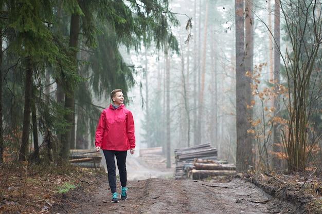 Caucasiana cabelos curtos, weared em capa de chuva rosa mulher sorridente andando na floresta nublada