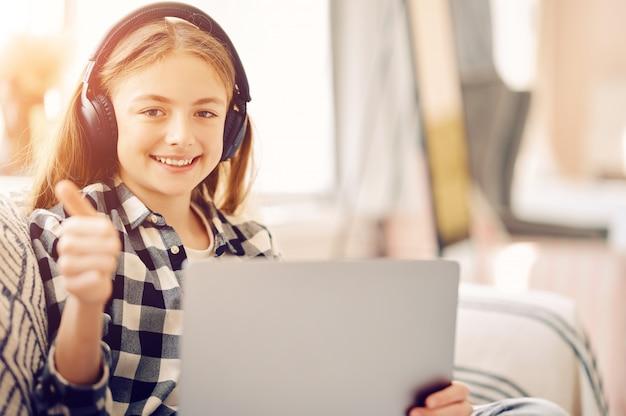 Caucasiana estudante média com laptop pc e fones de ouvido em casa
