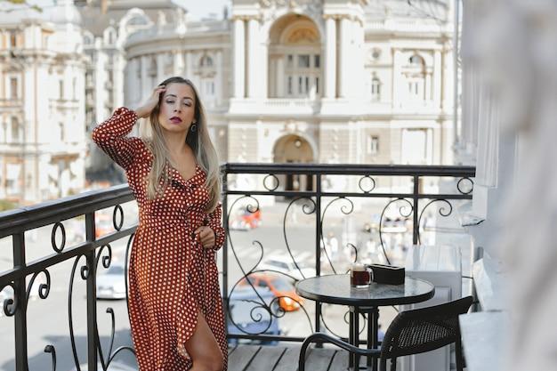 Caucasiana jovem atraente, vestida com um vestido de bolinhas vermelhas está de pé no terraço perto da mesa de café com vista para a rua da cidade, com velhos edifícios arquitetônicos