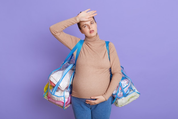 Caucasiana jovem linda grávida, cansada futura mãe sentindo cansaço e dor de cabeça, parece cansada e exausta, tocando sua testa, segurando duas bolsas, indo para a maternidade.