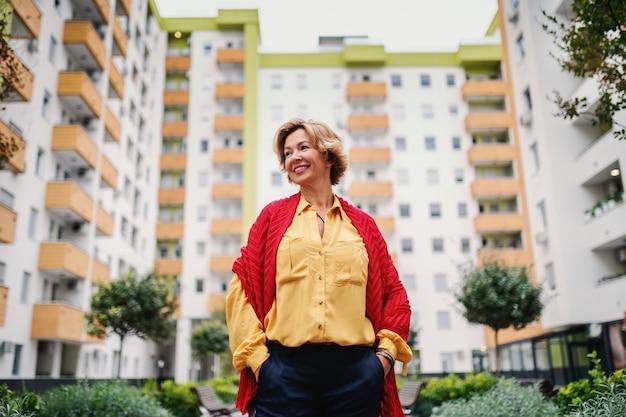 Caucasiana loira na moda sênior mulher bonita com cabelo curto e cachecol em pé no parque