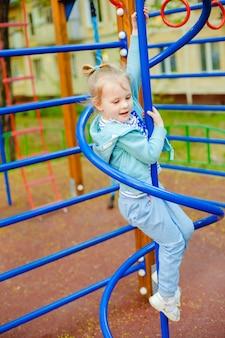 Caucasiana menina bonitinha loira se divertindo em um parque infantil ao ar livre no verão