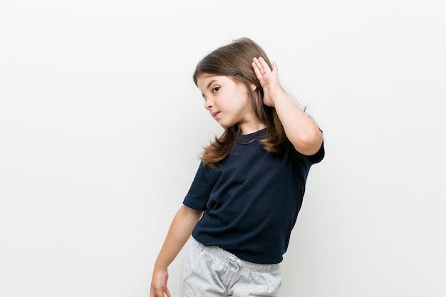 Caucasiana menina bonitinha tentando ouvir uma fofoca.
