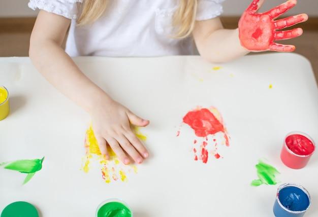 Caucasiana menina pintura com mãos coloridas pinta em casa educação infantil, preparando-se para o desenvolvimento da escola pré-escolar jogo para crianças