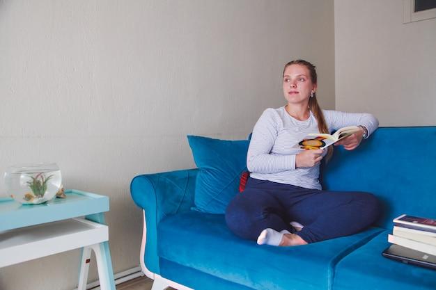 Caucasiana menina sentada no sofá com um livro nas mãos dela. ficar em casa conceito.