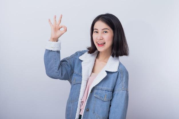 Caucasiana mulher sorridente, mostrando a mão com sinal ok