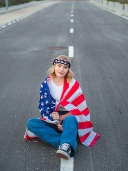 Caucasiana patriótica sentada no meio da estrada com a bandeira dos eua pendurada ao redor dela