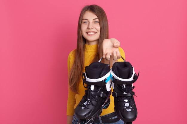 Caucasiana senhora sorridente segurando patins, mostrando seus equipamentos esportivos, passar o tempo de maneira ativa, senhora expressando emoções positivas.
