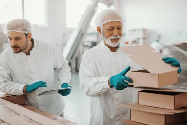 Caucasiana trabalhando sênior em uniforme branco colocando e preparando caixas, enquanto sorrindo, supervisor segurando o tablet e caixas de seleção. interior da planta alimentar.