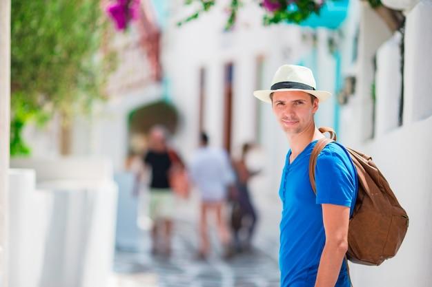 Caucasiana turista andando pelas ruas estreitas de mykonos. jovem rapaz urbano de férias para explorar a rua de paralelepípedos da cidade europeia