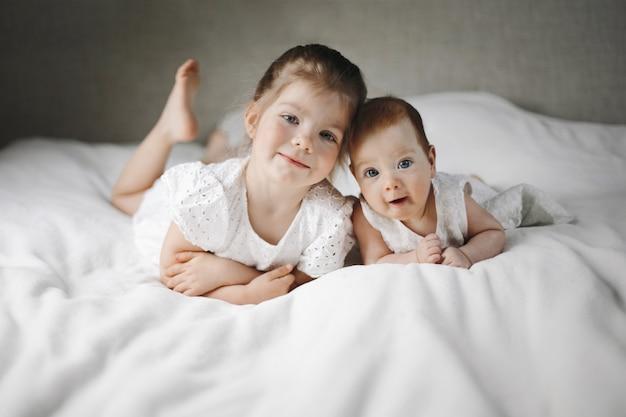 Caucasianas irmãzinhas estão deitado sobre o grande cobertor branco