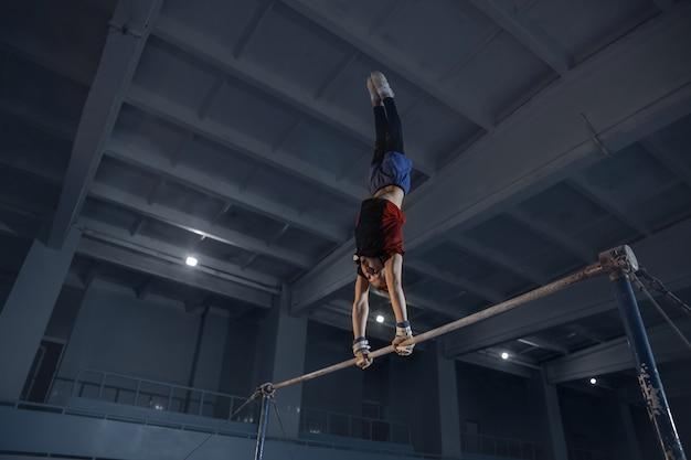 Caucasiano apto garotinho, atleta em roupas esportivas, praticando em exercícios para força e equilíbrio.