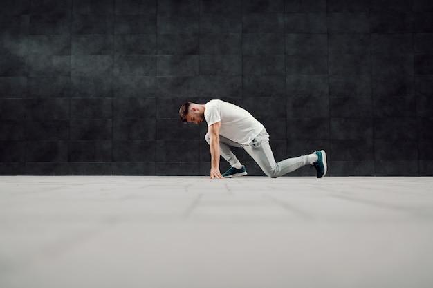 Caucasiano atraente encaixa esportista de agasalho e camiseta ajoelhado e se preparando para correr.