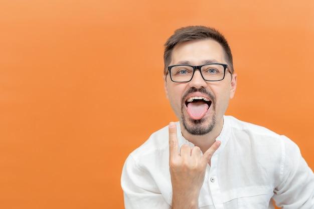 Caucasiano barbudo homem legal em óculos, mostrando a língua e o gesto de rock and roll em laranja