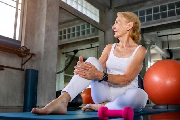 Caucasiano de mulher sênior sorrindo e feliz no ginásio de fitness.