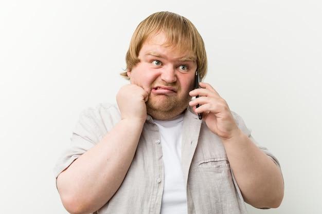 Caucasiano e mais homem tamanho chamando pelo telefone roer as unhas, nervoso e muito ansioso.