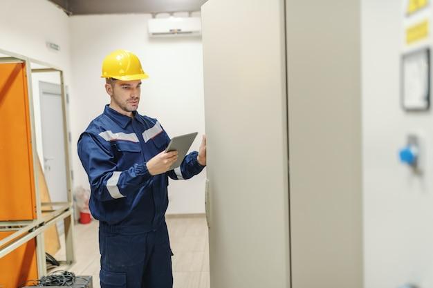 Caucasiano eletricista dedicado em uniforme e capacete na cabeça usando o tablet e abrindo a porta com painel em pé na sala de controle na planta da indústria pesada.