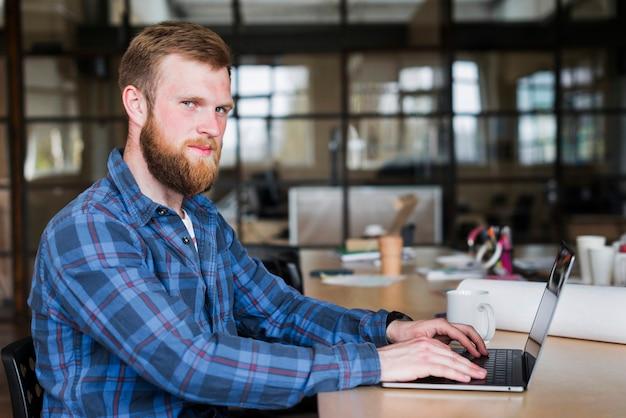 Caucasiano, homem jovem, sentando, frente, laptop, e, olhando câmera
