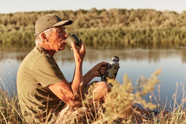 Caucasiano homem sênior bebendo café quente ar chá na beira do lago, atividade de aposentadoria de felicidade, aventura e viagens, homem vestindo trajes casuais relaxantes perto da água.