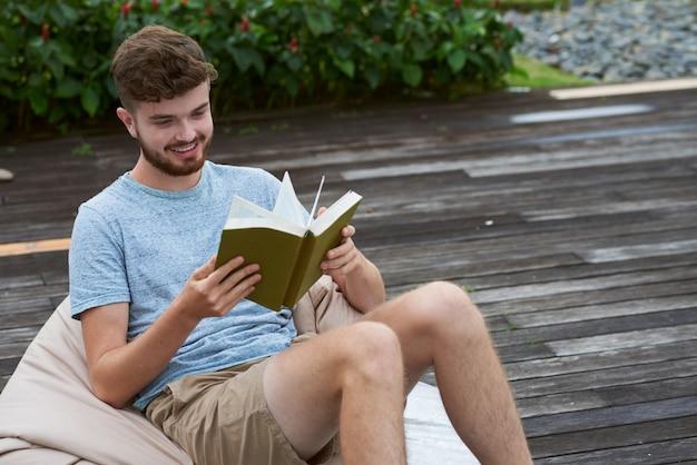 Caucasiano jovem alegre sentado na cadeira do saco de feijão ao ar livre e livro de leitura