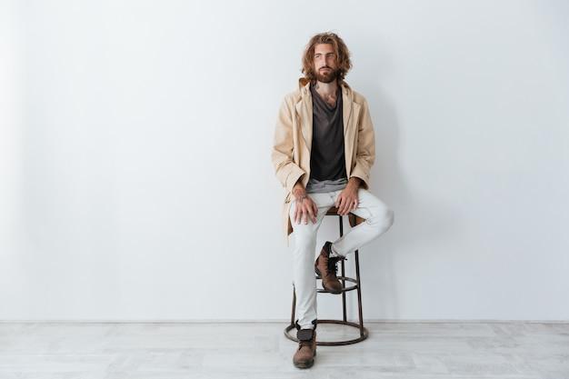 Caucasiano jovem barbudo sentado isolado sobre parede cinza