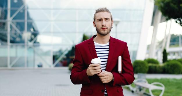 Caucasiano jovem bonito elegante empresário caminhando ao ar livre na cidade com o planejador e bebendo a bebida. edifício moderno do centro de negócios no fundo. masculino passeando e bebendo café para viagem.