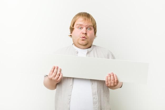 Caucasiano louco gordo loiro com um cartaz