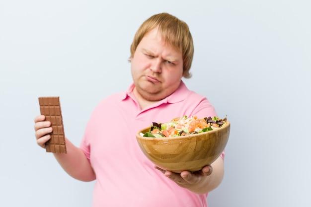 Caucasiano louco gordo loiro escolhendo entre tablete de chocolate ou saladeira