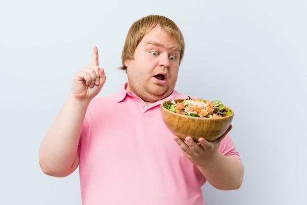 Caucasiano louco gordo loiro segurando uma tigela de salada