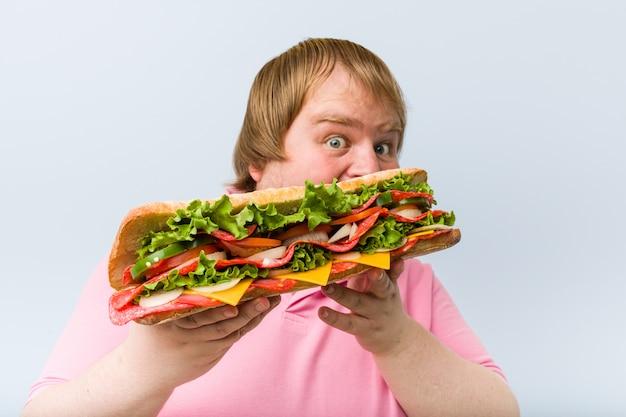 Caucasiano louco loiro gordo segurando um sanduíche gigante