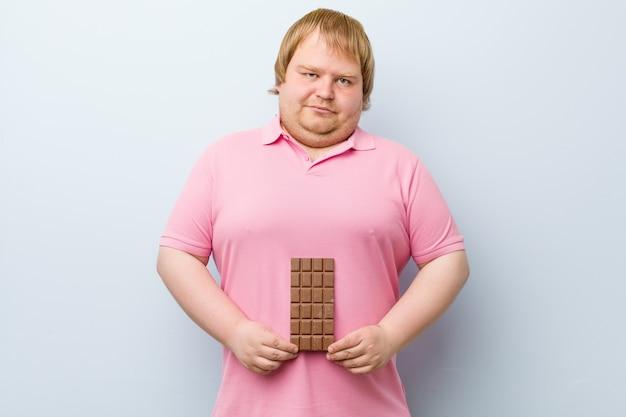 Caucasiano louro gordo segurando uma tablete de chocolate