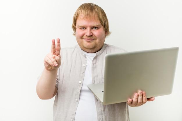 Caucasiano, mais tamanho homem segurando um laptop mostrando o número dois com os dedos.