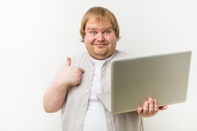 Caucasiano, mais tamanho homem segurando um laptop surpreendeu apontando para si mesmo, sorrindo amplamente.