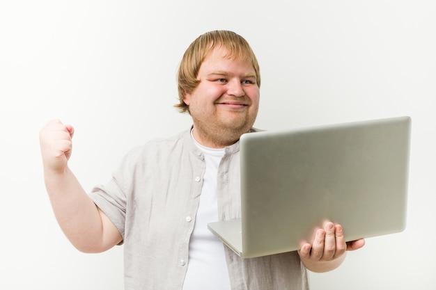 Caucasiano, mais tamanho homem segurando um laptop torcendo despreocupado e animado. conceito de vitória