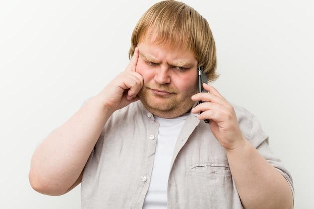 Caucasiano, mais tamanho homem telefonando, apontando seu templo com o dedo, pensando, focou uma tarefa.