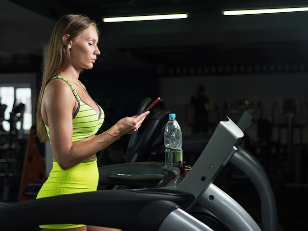 Caucasiano, menina, executando, ligado, um, treadmill, segurando, dela, telefone móvel, em, ginásio
